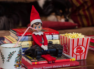 Elf on the shelf ready for some PS3 gaming with popcorn and coco