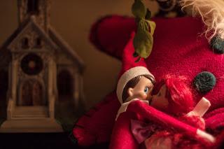 Elf on the shelf kisses red head barbie under the mistletoe