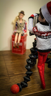 Elf on the shelf taking a photo of Barbie