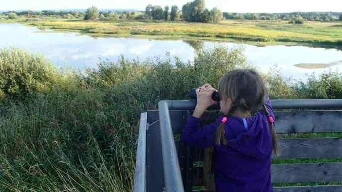 Kind schaut mit Fernglas über den See