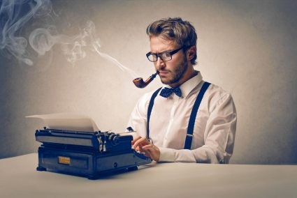 A man smoking a pipe while typing