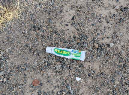 A tube of Polident laying on the ground