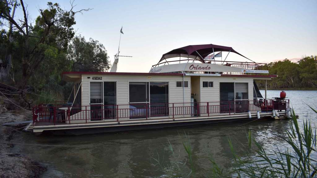 A houseboat moored at the riverbank.