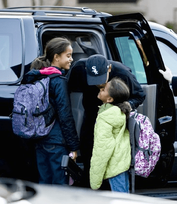 Under the spotlight Obama drops his kids off to school
