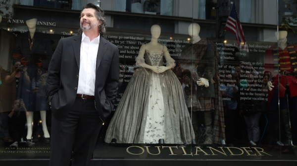 """Showrunner Ronald D. Moore unveils an exhibit of costumes from the first season of the STARZ Original Series """"Outlander"""" at The Grove in Los Angeles on Friday, May 22, 2015. (Photo by Matt Sayles/Invision for STARZ/AP Images)"""