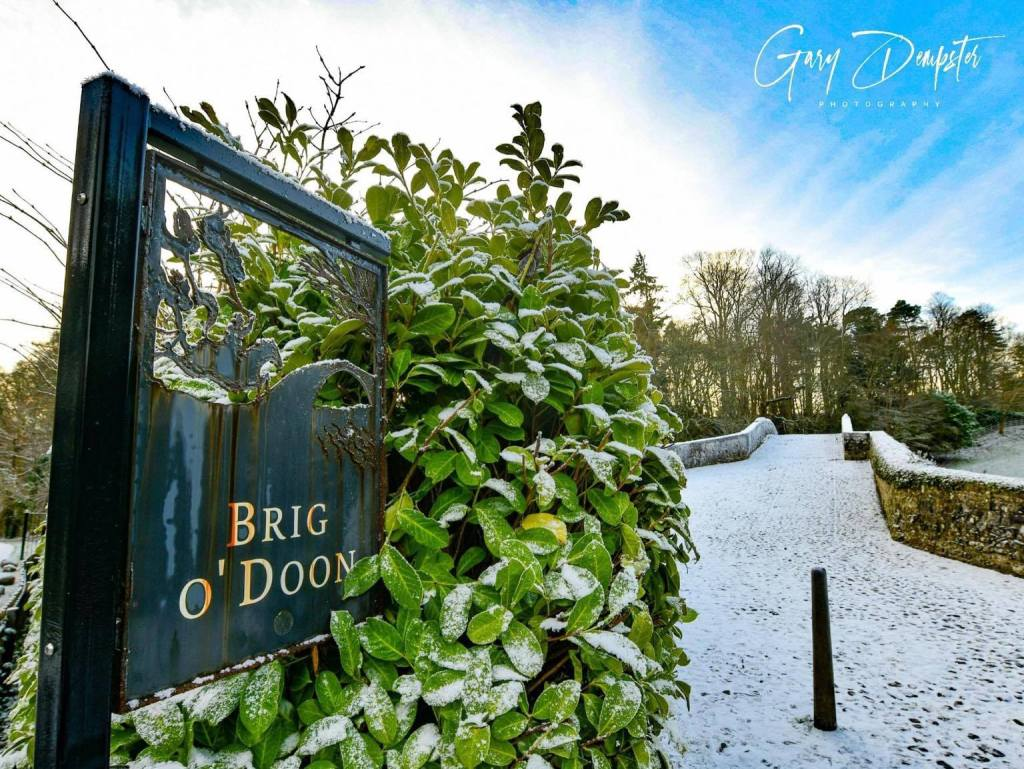snow covered sign that reads Brig o' Doon with snow-covered stone bridge beyond the sign
