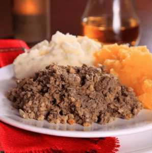 white plate holding haggis, neeps or rutabagas and tatties or potatoes with a small glass of whisky beside the plate