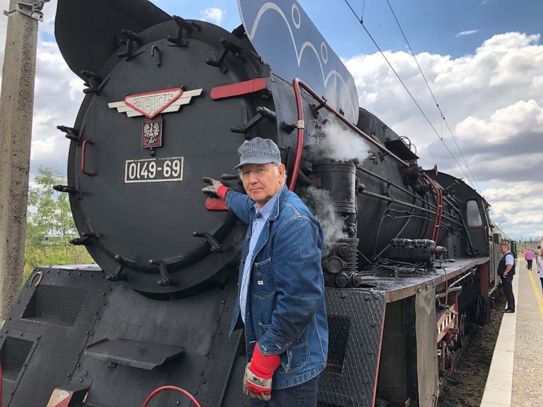 Man stands in front of train.