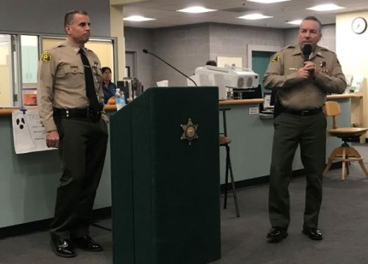 Los Angeles County Sheriff Alex Villanueva commands the microphone at a recent town hall at La Cañada High School as Capt. Todd Deeds of the Crescenta Valley Sheriff's Station stands by. Tanya Wilson, head of security at LCHS, is pictured in the background.