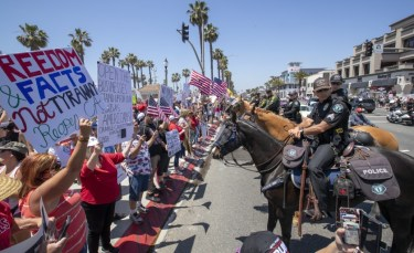 Mounted police line up to keep protesters on the sidewalk as thousands of protesters rally at the intersection of Main Street and Pacific Coast Highway in Huntington Beach.(Allen J. Schaben/Los Angeles Times)