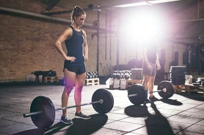 Two sportsmen standing near barbells in gym
