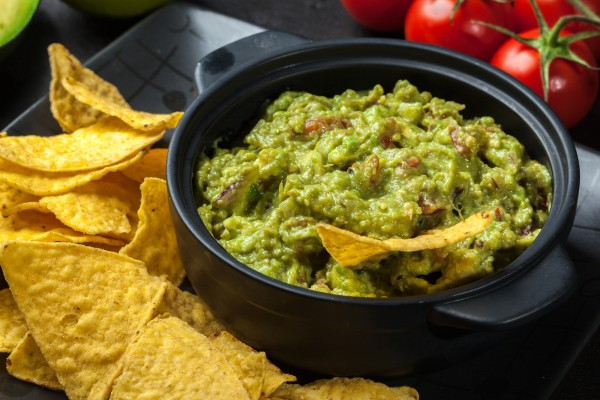Bowl of guacamole with corn chips on a black table