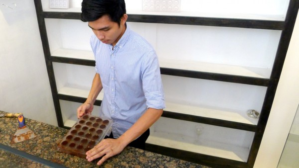Chocolatier demonstrates the art of molding tablea liquor