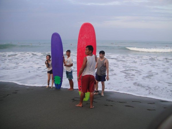 First-time surfers proudly pose with their boards and instructors