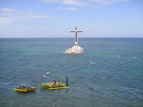 Small boats cruising towards the landmark cross above the Sunken Cemetery for a closer look