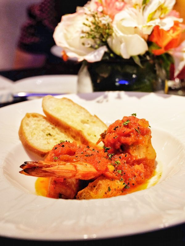 Seafood Skillet Stew served with baguette, capellini and arugula pasta