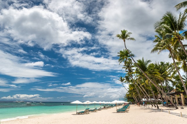 Tropical beach background from Alona Beach at Panglao Bohol island with beach chairs on the white sand beach with cloudy blue sky and palm trees. Travel Vacation