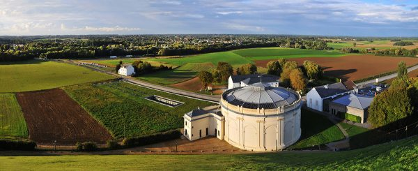 Panoramic view of the wide open fields where the Battle of Waterloo took place taken from the top of the Lion's Mound with the round theater in the foreground.