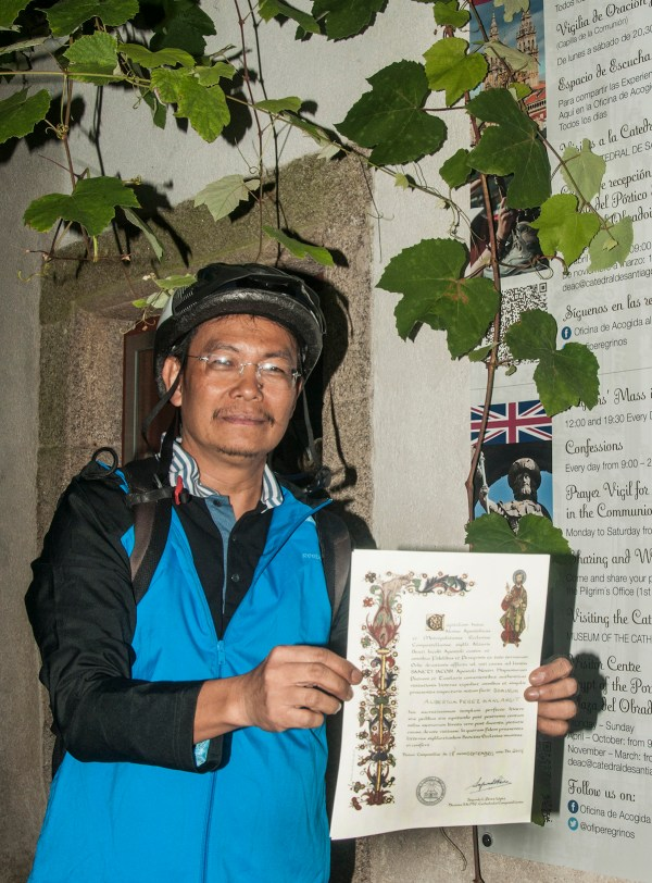 Holding my Compostela Certificate which they award to those who walked at least 100 kms. or biked 200 kms.