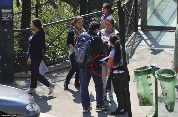 A Roma woman asks this man to sign a petition while an accomplice picks photo by Daily Mail