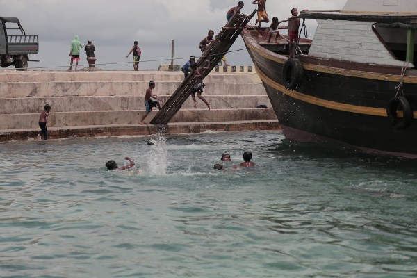 Children of Simunul bask in the afternoon sun, taking turns in diving from the boat deck.