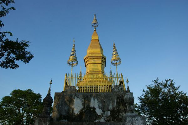 The gilded stupa of Wat Chom Si on the summit of Mount Phou Si by Allie Caufield via Wikipedia CC