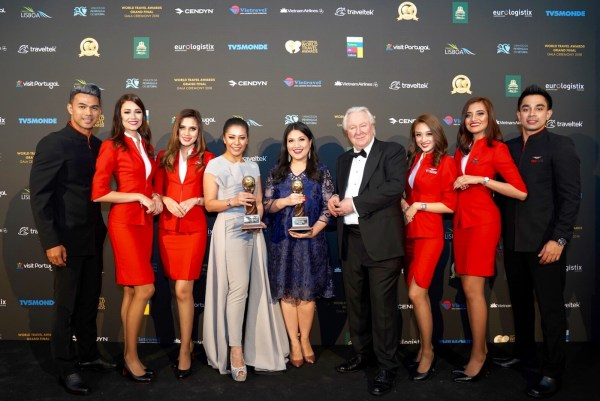 AirAsia Group Head of Cabin Crew Suhaila Hassan (centre left) and AirAsia Group Head of Communications Audrey Progastama Petriny (centre) accepted the World's Leading Low-Cost Airline and World's Leading Low-Cost Airline Cabin Crew awards from President & Founder of World Travel Awards Graham Cooke (centre right), flanked by AirAsia cabin crew.