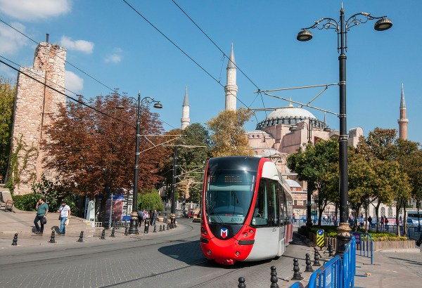 A modern streetcar passes by the main thoroughfare of the old city.