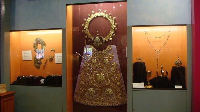 Old regalia of the image including its breastplate, halos, crowns, scepters, baton, and vestments at the museum. photo by Ramon FVelasquez via Wikipedia CC