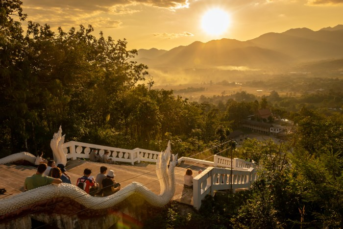 Tourists watch the sunset from White Buddha in Chedi Phra That Mae Yen, Pai, Thailand photo via Depositphotos