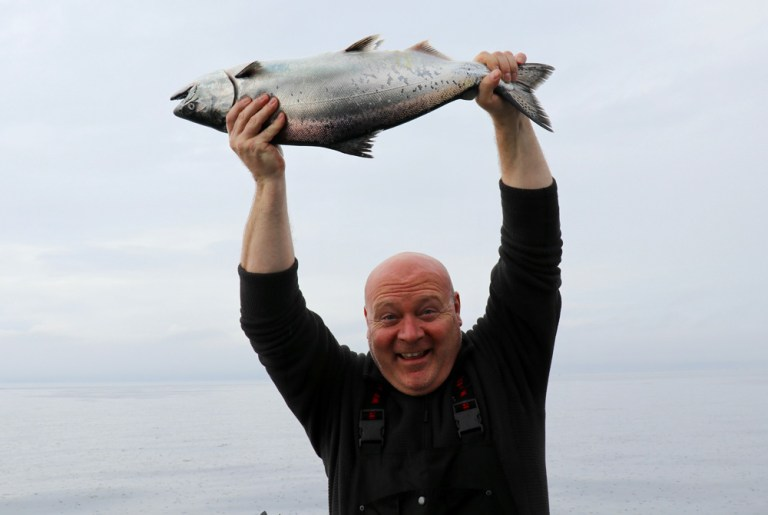 man holding king salmon in the rain bc fishing