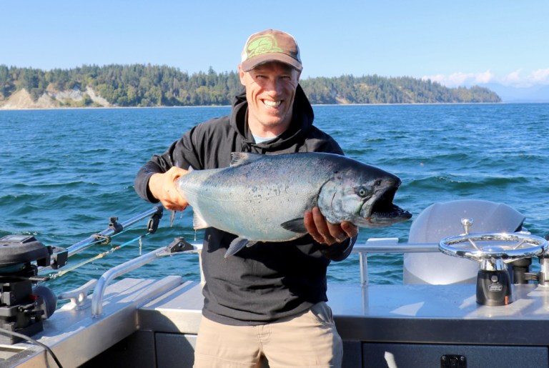 man holding king salmon up pacific northwest