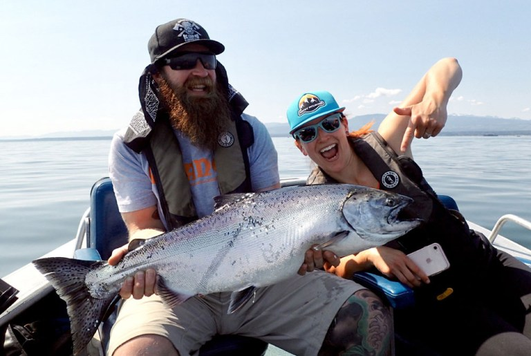 couple with woman pointing to large chinook salmon