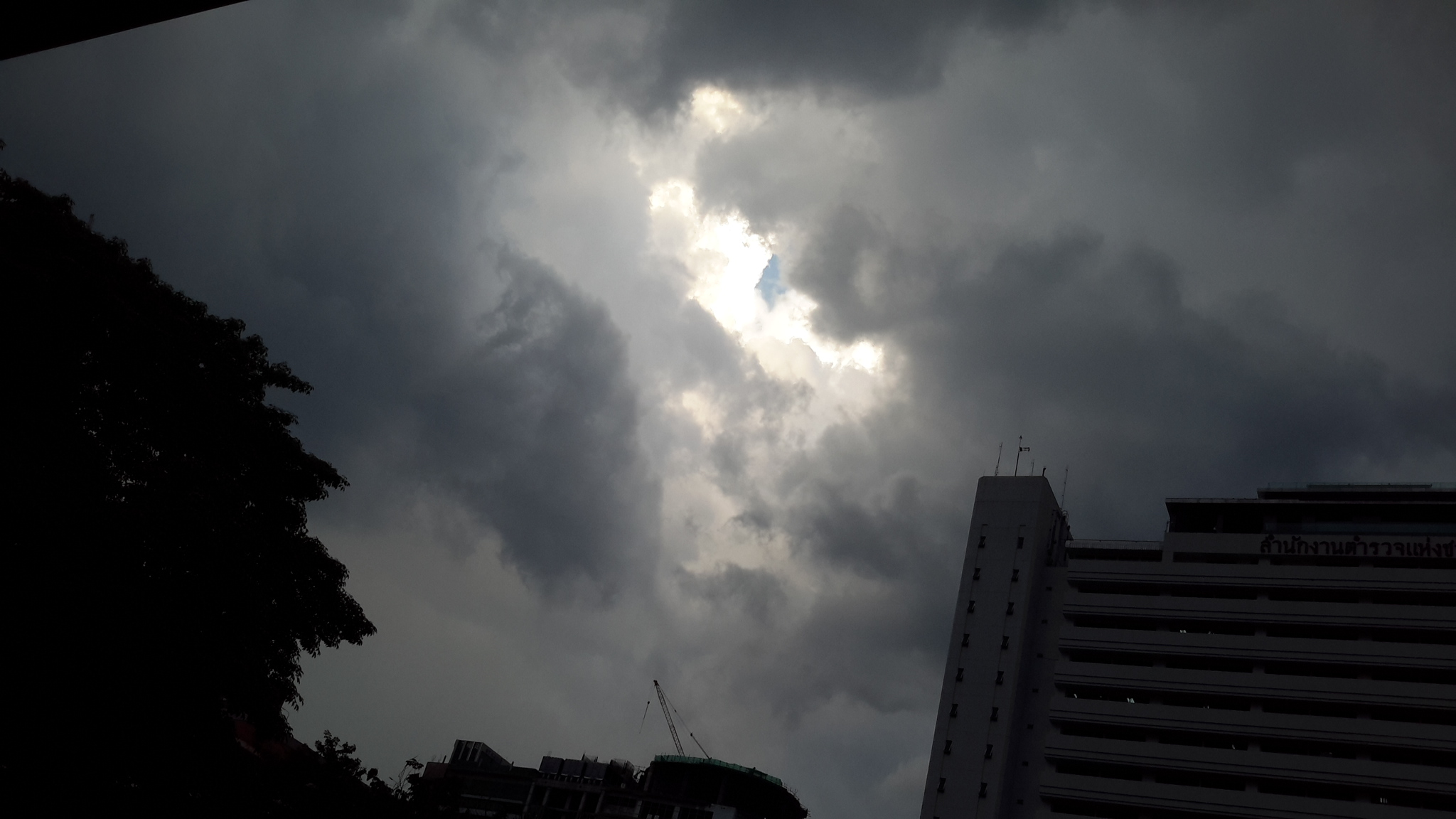 Little hole of light in the dark cloudy sky
