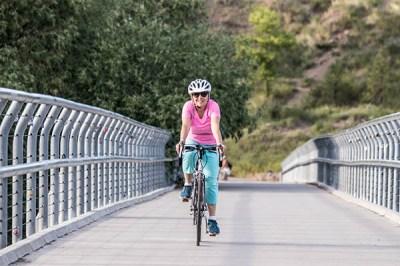 Photo of Lisa Brown biking across bridge.