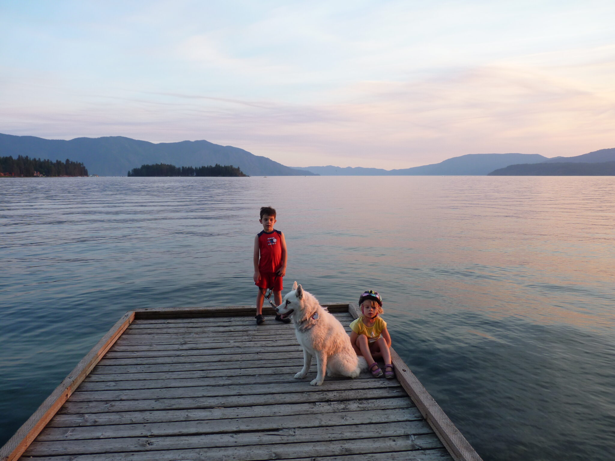 Two young children with their dock standing on a dock at sunset at Lake Pend Oreille, with forested hills in the far distance.