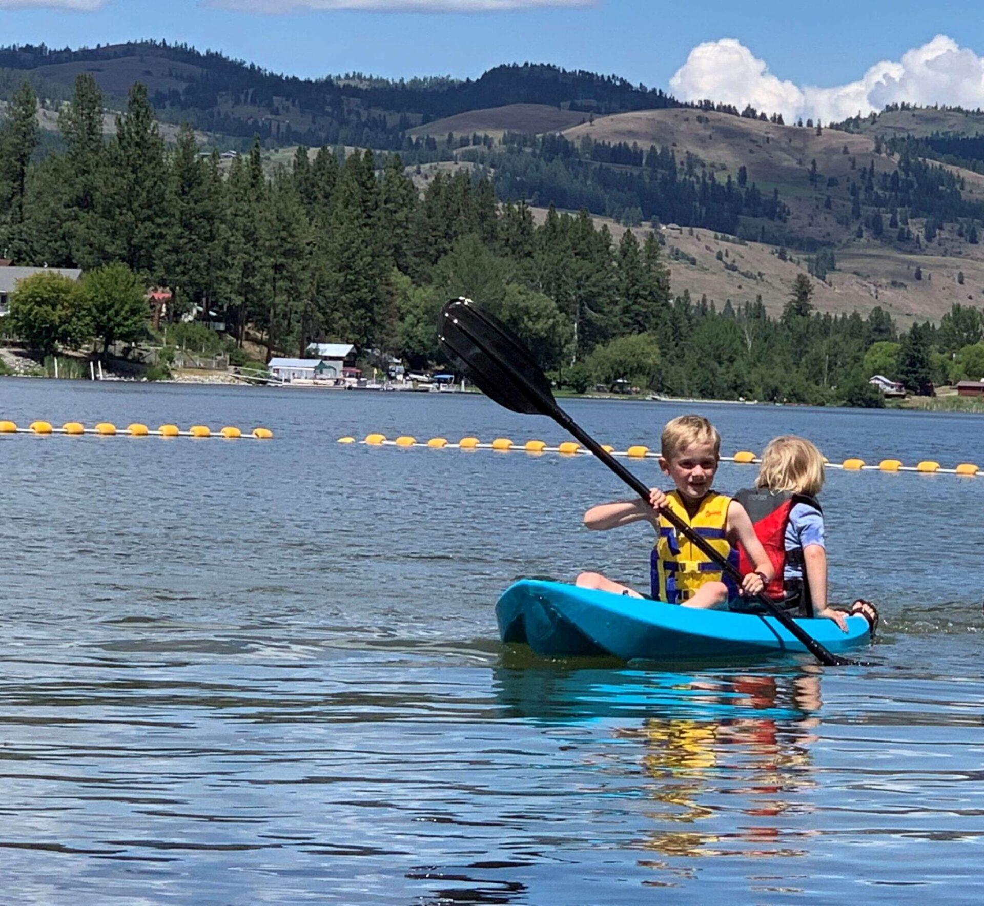 Two kids paddling on a lake.
