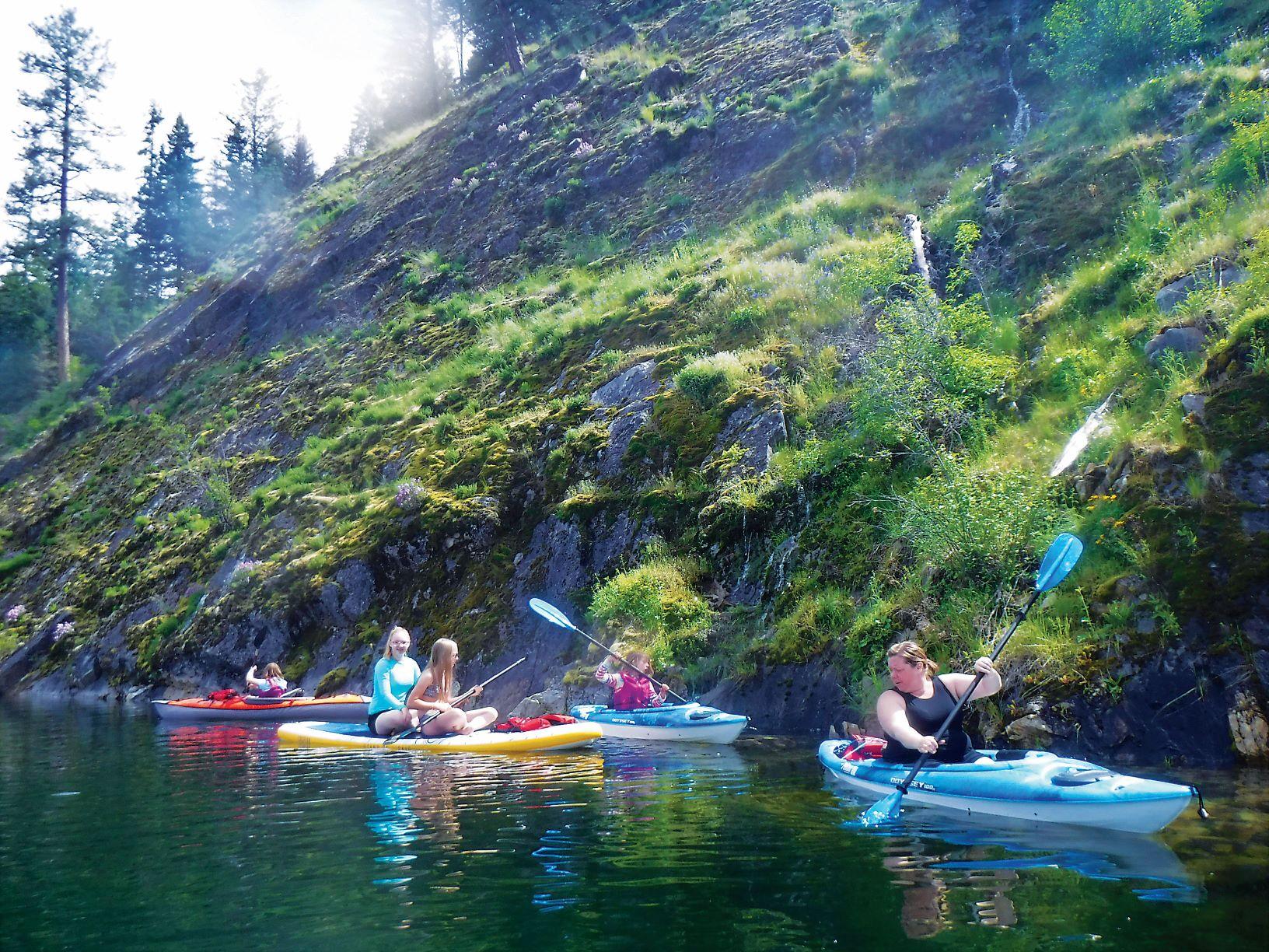 Mom and children kayaking near a rock cliff shoreline at Sullivan Lake.