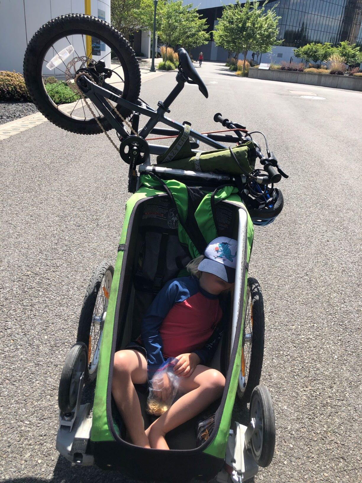 Child napping in a green bicycle trailer with child's bike attached to the back of trailer.