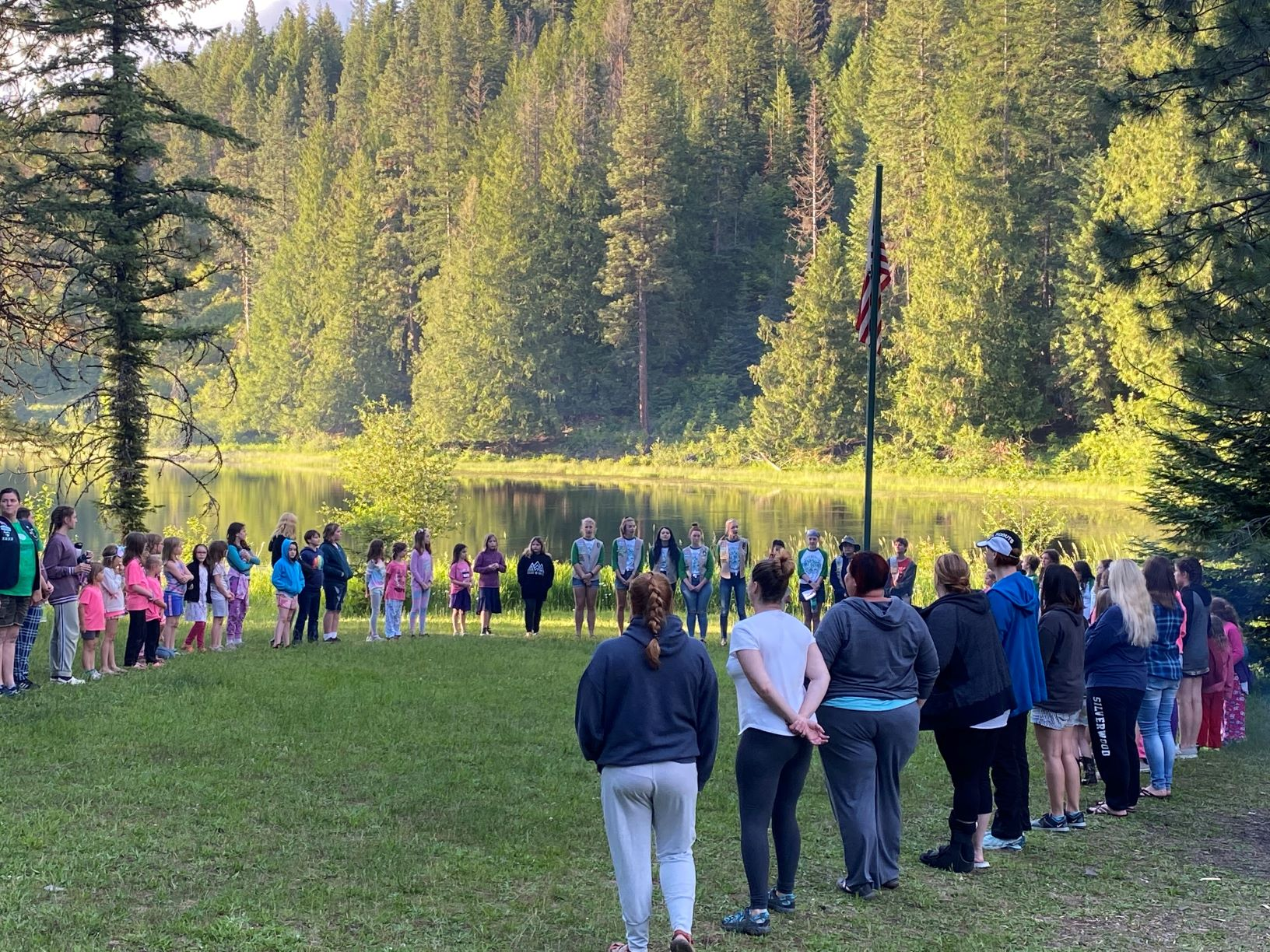 Girl Scout summer campers standing in a big circle on the grass, with Lake Coeur d'Alene and trees in the background.