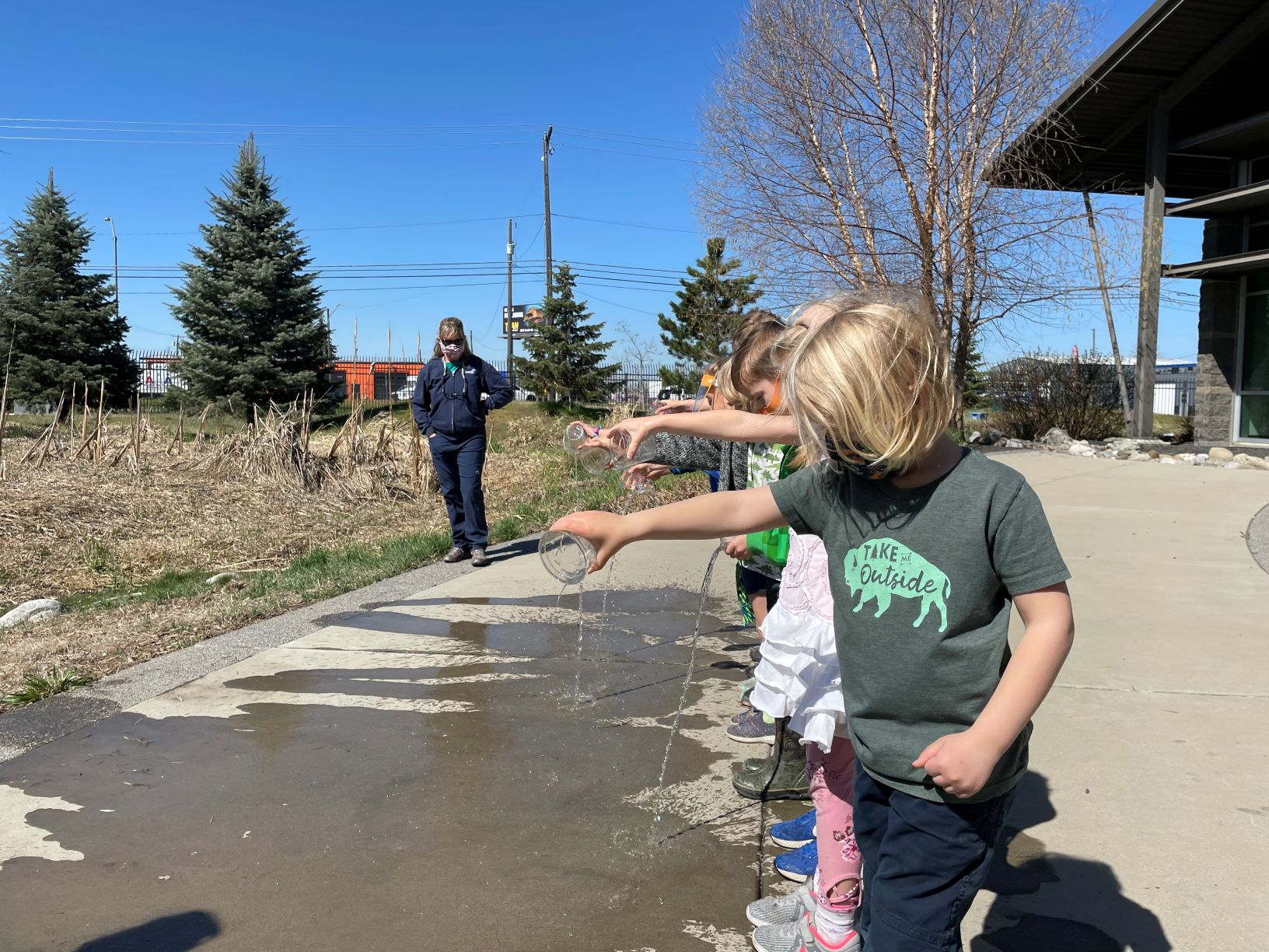 Students pouring water from cups onto the ground while learning at the Spokane County Water Resources Center. Instructor looks on.