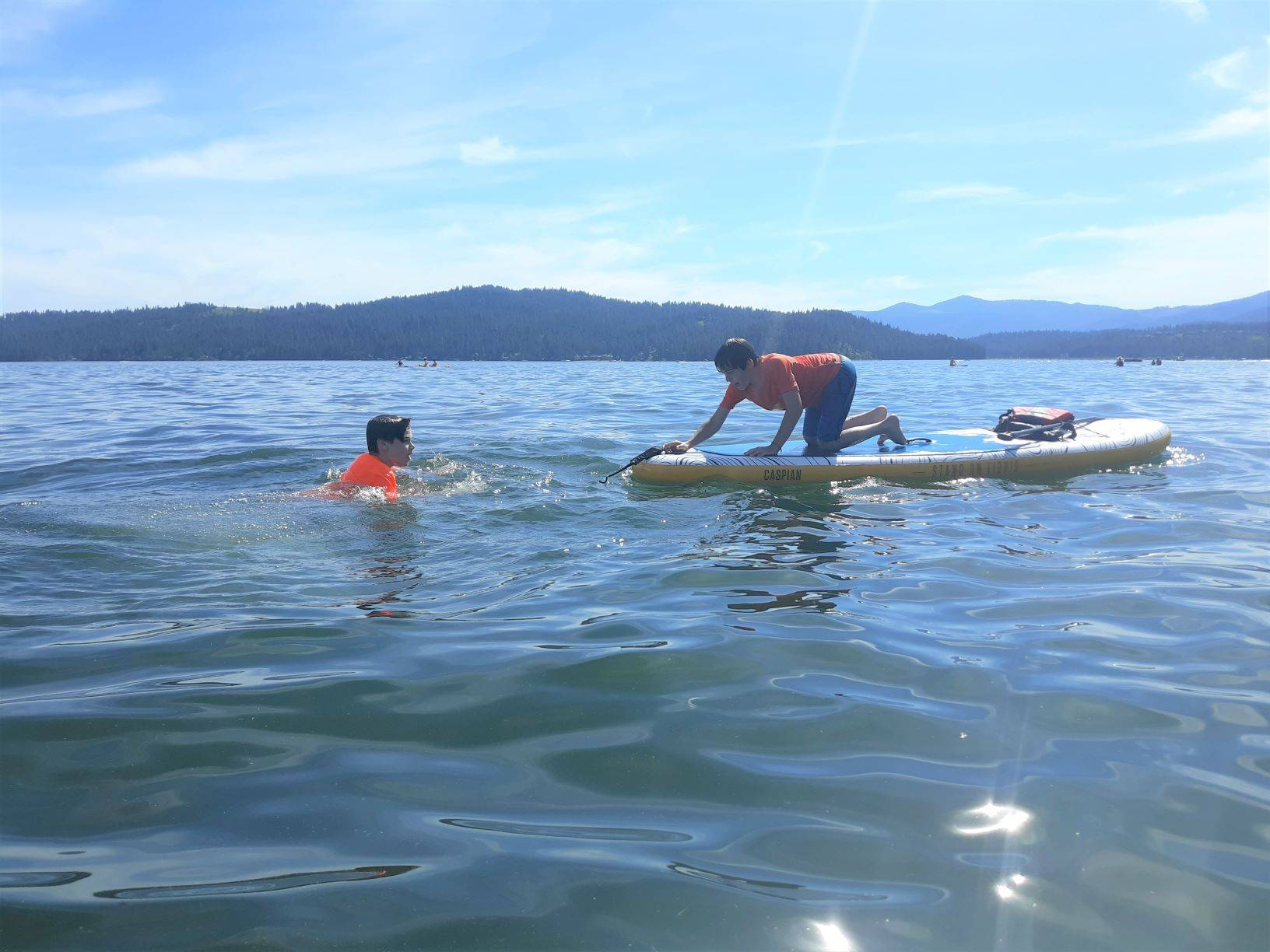 Two boys swimming in Lake Coeur d'Alene, one boy kneeling on a paddleboard. Sun shining on the water, and mountainous hills in the far background.