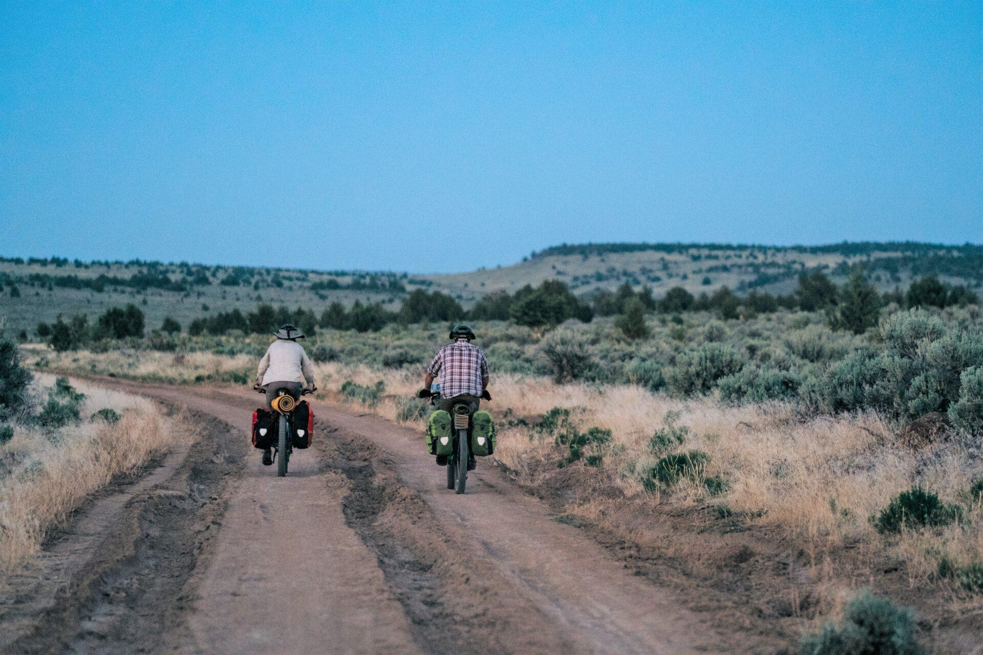 Biking dirt road up the shoulder of Steens Mountain, alongside sagebrush.