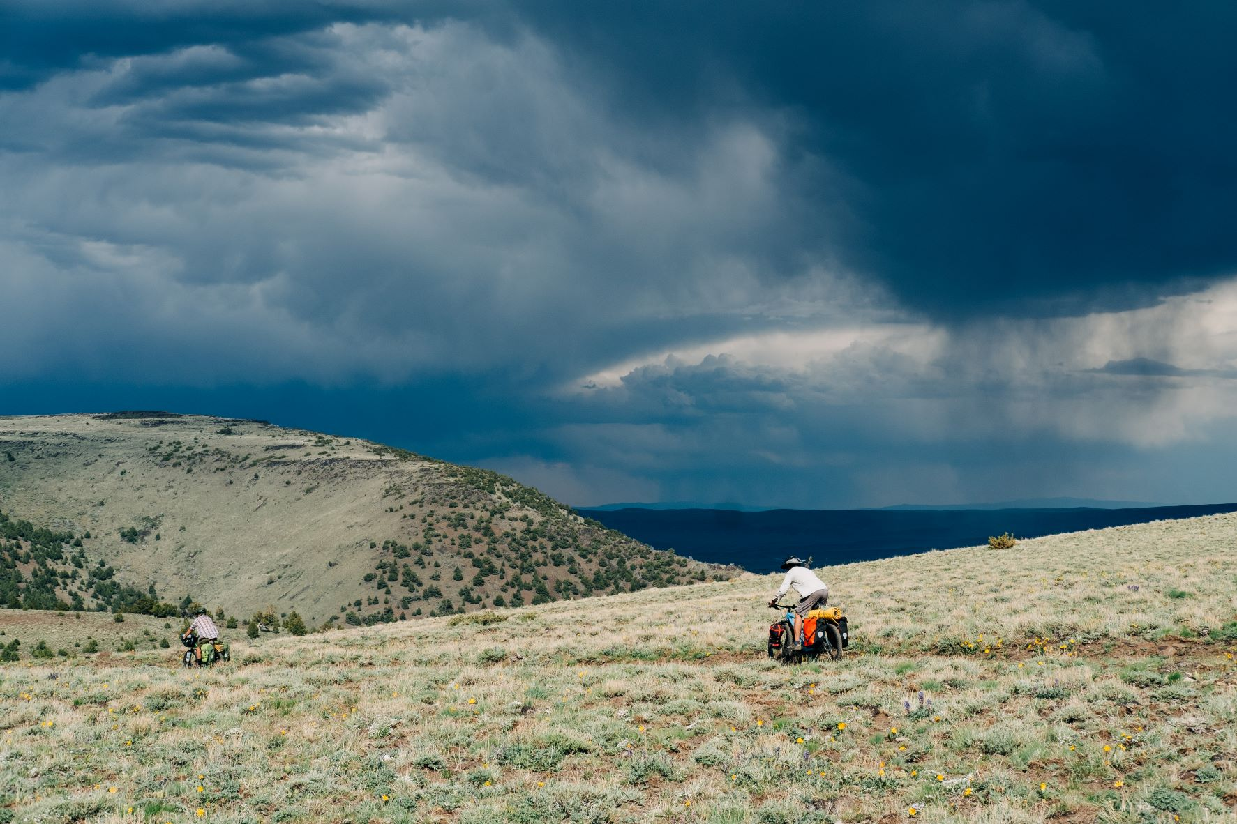 Biking down the east slope of Steens Mountain in Oregon, with dark storm clouds looming in the distance.