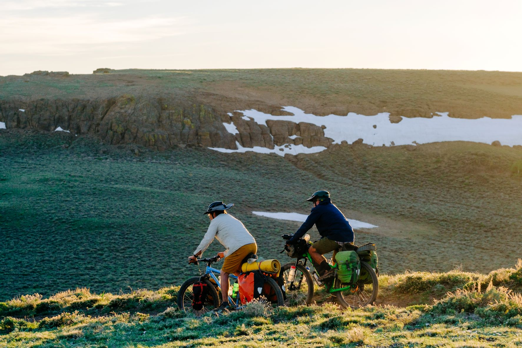 Two bikers along a dirt trail in te Trout Creek Mountains, with snow remnants on the shady rock cliffs in the distance.