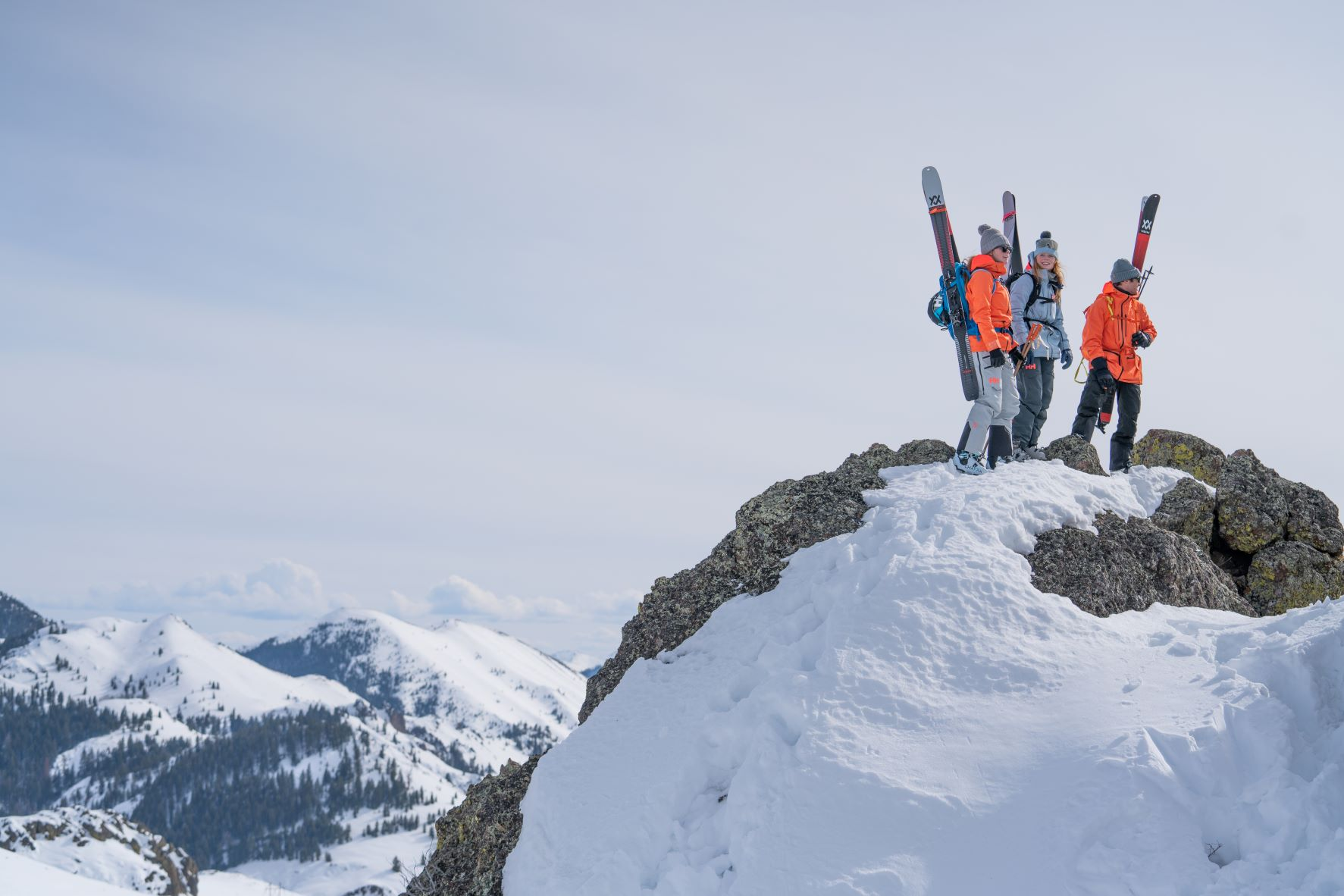Three skiers in their ski boots with skis attached to their backpacks as they stand atop a rock cliff on a mountain.