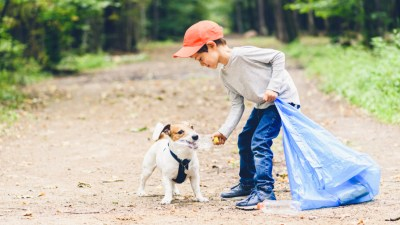dog and child picking up trash earth day every day