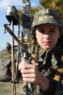 A picture of a female dressed in camouflage and holding a bow and arrow.
