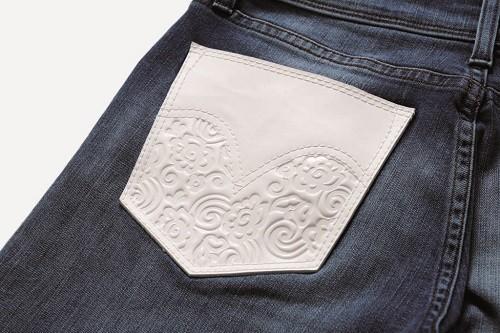 選用低腰窄管丹寧褲(Skinny Jeans),左側後口袋採用白色真皮並以蕾絲元素點綴