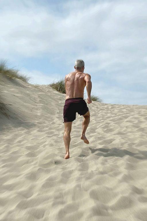 mature athlete running sprints at the beach